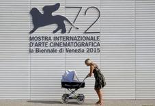 Mulher passa com seu carrinho de bebê em frente ao logo do Festival de Cinema de Veneza, na Itália, nesta terça-feira. 01/09/2015 REUTERS/Manuel Silvestri