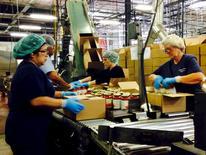 Trabajadores empaquetan frascos con salsa de tomate, en una planta dirigida por Chelten House Products, en Bridgeport, Nueva Jersey, 27 de julio de 2015. Los mercados laborales en Estados Unidos estaban lo bastante estrechos como para generar pequeñas ganancias en salarios en algunas profesiones en las últimas semanas, aunque algunas compañías están sintiendo el impacto por una desaceleración de la economía de China, dijo el miércoles la Reserva Federal. REUTERS/Jonathan Spicer
