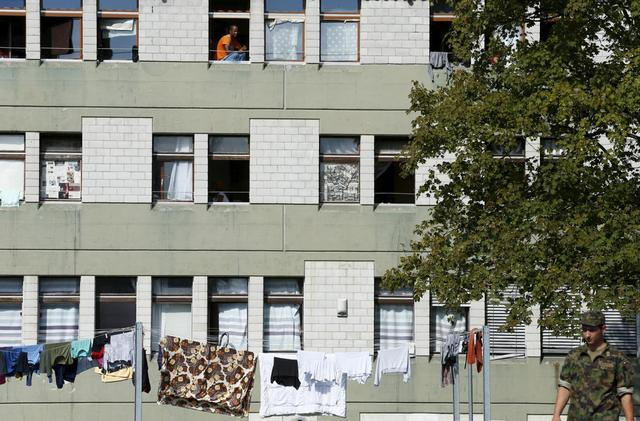 A refugee looks out of a window at a refugee camp in Lyss, Switzerland, September 2, 2015. REUTERS/Ruben Sprich