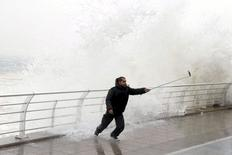 A man takes a selfie by a crashing wave on Beirut's Corniche, a seaside promenade, as high winds sweep through Lebanon during a storm in this February 11, 2015 file photo. REUTERS/Mohamed Azakir/Files