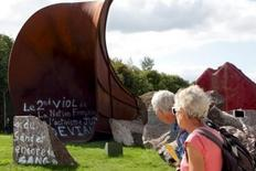 """Tourists look at the damaged """"Dirty Corner"""" installation by British-Indian sculptor Anish Kapoor at the Palace of Versailles, near Paris, France, September 6, 2015, after the second attack against the artwork in three months. A series of sentences, some of which were anti-Semitic, were painted on Kapoor's steel and rock sculpture. REUTERS/Philippe Wojazer"""