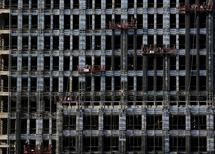 Labourers on lifts work on a new residential complex under construction in Beijing, in this November 18, 2013 file photo.  REUTERS/Kim Kyung-Hoon/Files