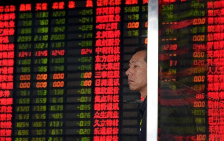 An investor stands in front of an electronic board showing stock information at a brokerage house in Shanghai, China, September 2, 2015.  REUTERS/China Daily