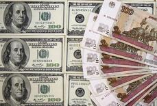 Долларовые и рублевые купюры в Сараево 9 марта 2015 года. Рубль оставался в нешироких диапазонах на торгах понедельника при низкой активности в американский праздник - День труда, из-за чего мировые рынки были малоликвидны и спокойны, при этом ослабела реакция на колебания нефти, которая провела время в основном на красной территории. REUTERS/Dado Ruvic