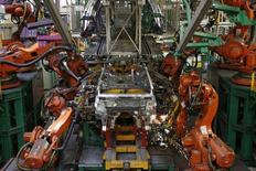 """Robots industriels dans une usine Renault à Flins (Yvelines). Pour Bruno Bonnell, un multi-entrepreneur lyonnais qui s'est vu confier par le gouvernement une mission pour organiser la filière robotique française, la robotisation de l'économie provoquera """"une avalanche d'emplois"""", contrairement aux idées reçues, et le retard français dans ce domaine peut être une chance pour équiper le pays en nouveaux robots de pointe. /Photo prise le 5 mai 2015/REUTERS/Benoît Tessier"""