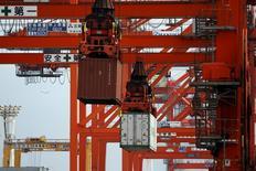 Краны перемещают контейнеры в порту Токио. 19 августа 2015 года. Экономика Японии сократилась во втором квартале не так сильно, как ожидалось, однако капитальные расходы упали сильнее прогнозов, свидетельствуют пересмотренные данные. REUTERS/Issei Kato