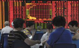 Inversores juegan a las cartas frente a un tablero electrónico que muestra la información de las acciones en una correduría en Shanghái, China, 9 de septiembre de 2015. La medicina amarga para los mercados de valores de China ha llevado estabilidad a los precios, al menos por ahora, pero ha tenido un costo: el comercio de las acciones y futuros ha caído a niveles tan débiles que corre el riesgo de volverse imperceptible. REUTERS/China Daily