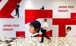 Мужчина проходит мимо рекламы Japan Post в офисе компании в Токио 26 июня 2015 года. Japan Post Holdings Co, а также входящие в группу банк и страховая компания планируют привлечь в ходе IPO в сумме $11,5 миллиарда, активизировав розничных инвесторов и оказав поддержку местному фондовому рынку. REUTERS/Thomas Peter