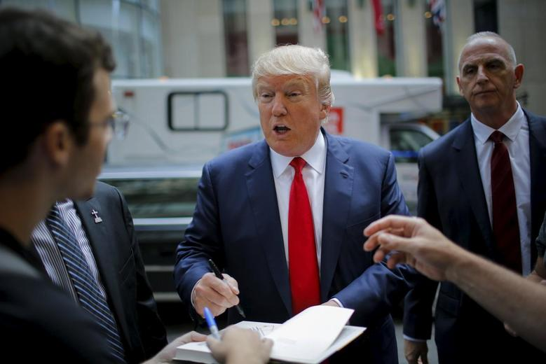 Republican presidential candidate Donald Trump signs autographs as he arrives to attend the Jimmy Fallon show in the Manhattan borough of New York, September 11, 2015. REUTERS/Eduardo Munoz