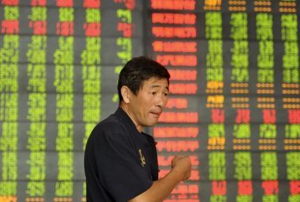 An investor speaks in front of an electronic board showing stock information at a brokerage house in Fuyang, Anhui province, China, September 14, 2015. REUTERS/Stringer