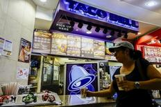 A woman buys products at a Taco Bell restaurant in Paramus, New Jersey July 8, 2015.  REUTERS/Eduardo Munoz