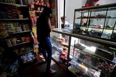 Una ex rebelde que ahora tiene una pequeña tienda en su casa trabaja en el mostrador, en Bogotá, 3 de febrero de 2015. La confianza del consumidor colombiano se desplomó en agosto, pisando terreno negativo por primera vez desde abril del 2009, debido a una fuerte caída en las condiciones económicas actuales de los hogares, mostró el martes una encuesta de la firma de estudios privados Fedesarrollo. REUTERS/Jose Miguel Gomez