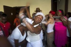 Practicantes de la santería se someten a un breve ataque de convulsiones inducidas por espíritus durante una ceremonia para atraer a los espíritus de los antepasados muertos para pedir orientación en el centro de La Habana, foto tomada el 18 de agosto de 2015. REUTERS/Alexandre Meneghini.