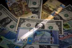 Банкноты тенге и доллара США. Алма-Ата, 21 августа 2015 года. Казахстанский тенге на межбанке после основной торговой сессии пробил психологически важную отметку в 300 тенге за $1, впервые после того, как Нацбанк отпустил валюту в свободное плавание. REUTERS/Shamil Zhumatov