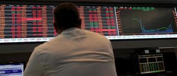 Мужчина смотрит на экран с графиком котировок акций, торгующихся на бирже Сан-Паулу Bovespa. Сан-Паулу, 10 сентября 2015 года. Несмотря на то, что рынки уже давно ожидают повышения процентных ставок ФРС в этом году, вероятность их повышения в сентябре снизилась, и если центробанк все же поднимет ставки в четверг, это может стать неприятным сюрпризом для развивающихся рынков. REUTERS/Paulo Whitaker
