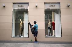 El grupo textil gallego Inditex cerró el primer semestre con un fuerte aumento del beneficio, impulsado por la recuperación económica en España y la debilidad del euro, que refuerza sus ventas fuera de la eurozona, lo que le permitía ganar más de un 3 por ciento en las primeras operaciones en bolsa. En la imagen, un hombre junto a una tienda de Zara en Madrid el 10 de junio de 2015.  REUTERS/Andrea Comas