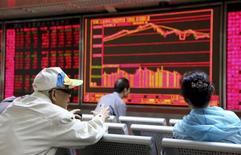 China está ampliando su control sobre los mercados continentales a las bolsas de comercio de materias primas, asustada por las señales de que los especuladores han pasado de sus volátiles mercados de valores a los futuros de las materias primas. En la imagen, inversores conversan frente a pantallas electrónicas con información bursátil en una casa de valores de Pekín el 16 de septiembre de 2015. REUTERS/Stringer