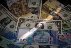 Купюры валют тенге и доллар США в Алма-Ате, Казахстан 21 августа 2015 года.  Национальный банк Казахстана в среду впервые вышел на рынок с интервенциями в попытке удержать падающий тенге, после того как валюта пробила на межбанке психологически важную отметку 300 тенге за $1. REUTERS/Shamil Zhumatov