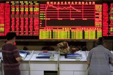 Inversores miran unas pantallas de computador frente a un tablero electrónico que muestra la información de las acciones, en una correduría en Shanghái, China, 7 de septiembre de 2015. Las acciones chinas cayeron un 2 por ciento el jueves, luego de que un declive en los últimos 30 minutos de comercio borró unas ganancias tempranas, lo que subraya la fragilidad de la confianza de los inversores en momentos en que la campaña anticorrupción de Pekín se extiende a través de la industria financiera. REUTERS/Aly Song