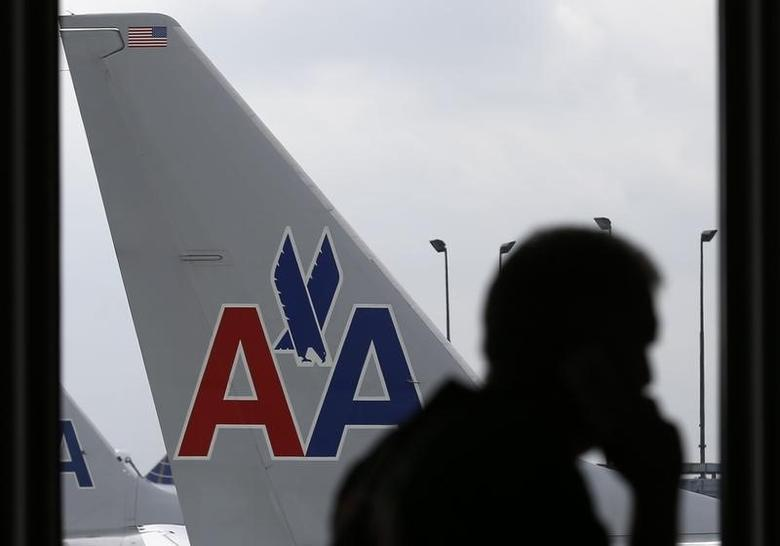 A passenger walks by an American Airlines airplane at a gate at the O'Hare Airport in Chicago, Illinois October 2, 2014. REUTERS/Jim Young