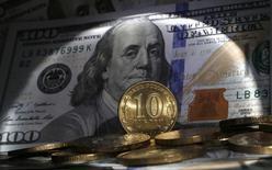 Рублевые монеты на фоне долларовой купюры в Санкт-Петербурге 22 октября 2014 года. Рубль завершил торги снижением к доллару, проведя торги в диапазоне 65,60-66 рубля за $1, и сохраняет шансы на рост до конца месяца в основном благодаря локальным факторам. Решение ФРС не менять ставку не вызвало на локальном рынке приступа сильного оптимизма: градус неопределенности будет высоким, обещая прежнюю волатильность на финансовом рынке РФ.  REUTERS/Alexander Demianchuk