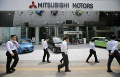 Men walk in front of Mitsubishi Motors Corp's headquarters in Tokyo May 23, 2013.   REUTERS/Toru Hanai