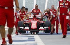 Ferrari Formula One team members push the car of driver Germany's Sebastian Vettel in pit lane before the third practice session of the Singapore F1 Grand Prix at the Marina Bay street circuit September 19, 2015. REUTERS/Edgar Su