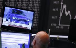 A Volkswagen Tiguan car appears in a news broadcast on a TV in front of the German share price index DAX board, at the stock exchange in Frankfurt, Germany September 21, 2015.  REUTERS/Ralph Orlowski
