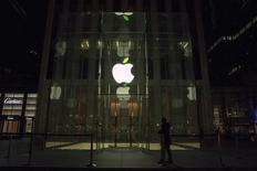 An employee stands in front of the Apple flagship store on 5th Avenue in New York April 22, 2015. REUTERS/Brendan McDermid