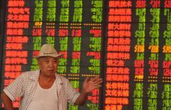 Un inversor frente a un tablero electrónico que muestra la información de las acciones, en una correduría en Fuyang, 23 de septiembre de 2015. Las acciones chinas cayeron el miércoles, golpeadas por la debilidad de la actividad fabril en el país que avivó los temores a una fuerte desaceleración económica. REUTERS/Stringer
