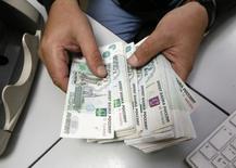 Человек пересчитывает рублевые купюры в офисе частной компании в Красноярске 17 декабря 2014 года. ЦБР оценил рынок теневой обналички через схемы с платежными агентами в 2014 году в 900 миллиардов рублей, что по масштабам превышает аналогичные операции в банковском секторе, и сообщил, что к сентябрю практически перекрыл этот канал. REUTERS/Ilya Naymushin