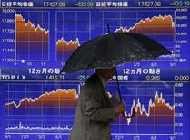 Un hombre camina junto a un tablero electrónico que muestra el índice Nikkei, afuera de una correduría en Tokio, 8 de septiembre de 2015. Las bolsas de Asia se encaminaban el miércoles a su mayor caída diaria en un mes después de que la actividad fabril en China se contrajo más que lo esperado, lo que se suma a los temores sobre un debilitamiento de la economía mundial e hizo que los inversores buscaran activos más seguros. REUTERS/Issei Kato
