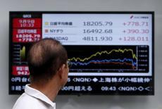 Un peatón mira un tablero electrónico que muestra la gráfica de fluctuación del índice Nikkei, el Dow Jones y el NASDAQ, afuera de una correduría en Tokio, Japón, 9 de septiembre de 2015. La mayoría de las bolsas de Asia cedía el jueves después de que unas noticias económicas pesimistas desde China y Estados Unidos aumentaron la presión sobre los activos de mayor riesgo. REUTERS/Yuya Shino