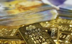 Barras de oro y billetes de francos suizos vistos en esta ilustración fotográfica tomada en Viena, 13 de noviembre de 2014. El regulador de la competencia en Suiza inició una investigación sobre una posible colusión de precios en el mercado de los metales preciosos por parte de importantes bancos, dijo el lunes el organismo, en la última de una serie de indagaciones sobre la fijación de los valores del oro, plata, platino y paladio. REUTERS/Leonhard Foeger