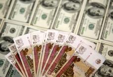 Рублевые и долларовые купюры в Сараево 9 марта 2015 года. Рубль в минусе утром вторника после существенного падения нефтяных котировок накануне и по окончании сентябрьского налогового периода. Далее влияние на котировки, помимо динамики нефти, могут оказывать локальные денежные потоки конца квартала. REUTERS/Dado Ruvic