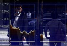 Un hombre se refleja en un tablero que muestra el índice Nikkei, afuera de una correduría en Tokio, Japón, 29 de septiembre de 2015. Las bolsas de Asia se desplomaban el martes a mínimos en tres años y medio y el dólar se hundía, arrastrado por unas fuertes pérdidas en Wall Street luego de que unos débiles datos chinos reavivaron las preocupaciones sobre su frágil economía. REUTERS/Issei Kato