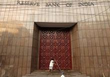 Una mujer limpia las escaleras del Banco de la Reserva de India, en Kolkata,  18 de diciembre de 2013. December 18, 2013. El Banco de Reserva de India bajó el martes su tasa de interés a un mínimo de 4 años y medio, a un 6,75 por ciento, en un recorte más fuerte de lo esperado, lo que podría ayudar a impulsar una economía que ha estado desacelerándose y que registra niveles mínimos de inflación. REUTERS/Rupak De Chowdhuri