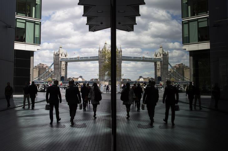 City workers are reflected in a window as they pass near the Tower of London in London, Britain April 28, 2015.  REUTERS/Neil Hall