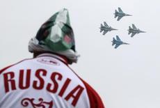"""Мужчина наблюдает за полетом истребителей Су-30СМ на авиашоу в Жуковском 29 августа 2015 года. Западные источники и противники сирийского президента Башара Асада говорят, что первые авиаудары российских ВВС по Сирии пришлись не по позициям """"Исламского государства"""", а по районам, которые контролирует прозападная сирийская оппозиция, и унесли жизни мирных жителей. REUTERS/Maxim Shemetov"""