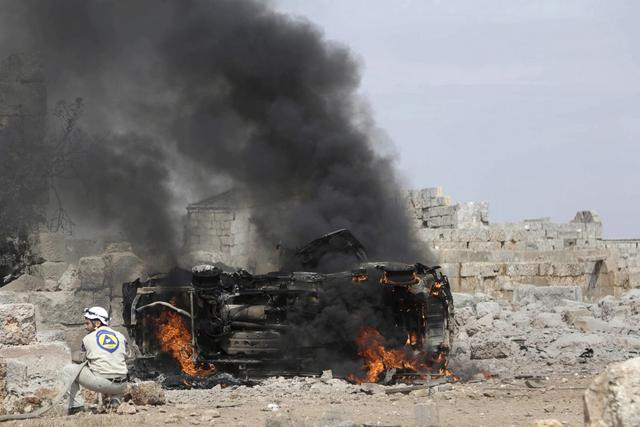 A civil defense member tries to put out the flames on a burning military vehicle at a base controlled by rebel fighters from the Ahrar al-Sham Movement, that was targeted by what activists said were Russian airstrikes at Hass ancient cemeteries in the southern countryside of Idlib, Syria October 1, 2015. REUTERS/Khalil Ashawi