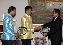 Tennis players Novak Djokovic (C) of Serbia and Rafael Nadal (L) of Spain give rackets to Thai Prime Minister Prayut Chan-o-cha (R) during a meeting at the Government House in Bangkok, Thailand, October 2, 2015. REUTERS/Rungroj Yongrit/Pool