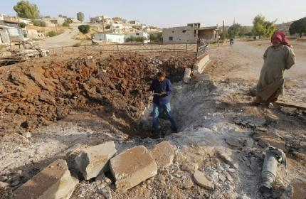Men stand along a crater caused by what activists said was a Russian air strike in Latamneh city on Wednesday, in the northern countryside of Hama, Syria October 2, 2015. REUTERS/Ammar Abdullah