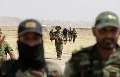 """Бойцы шиитской группировки """"Асаиб Ахли аль-Хак"""" и члены курдских военнизированных формирований пешмерга у города Сулейман-Пек в Ираке 1 сентября 2014 года. Представитель одной из наиболее влиятельных шиитских группировок Ирака заявил в понедельник, что она полностью поддерживает интервенцию и авиаудары России против """"Исламского государства"""" на Ближнем Востоке, и обвинил США в нерешительности действий против ИГИЛ. REUTERS/Youssef Boudlal"""