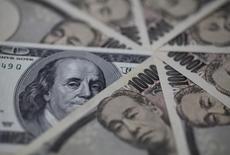 Банкноты доллара США и японской иены. Токио, 28 февраля 2013 года. Курс доллара к иене держится вблизи недельного максимума за счет повышенного спроса на рискованные активы и вероятности дальнейшего смягчения политики Банка Японии. REUTERS/Shohei Miyano