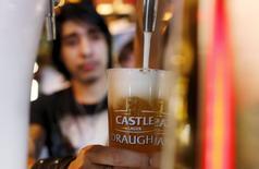 Un camarero sirve una cerveza de SAB Miller en Ciudad del Cabo, Sudáfrica, el 16 de septiembre de 2015. Anheuser-Busch InBev, la mayor cervecera del mundo, lanzó el miércoles una oferta mejorada por SABMiller, ofreciendo poco más de 68.000 millones de libras esterlinas (104.000 millones de dólares) por su mayor rival para extender su posición en África y otros mercados.  REUTERS/Mike Hutchings