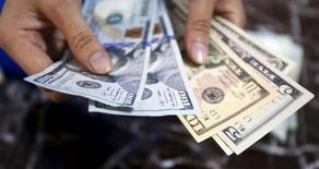 Un empleado contando dólares en una casa de cambios en Hanoi, ago 12, 2015. La posibilidad de que el dólar mantenga su fortaleza depende fundamentalmente de cuánto más demore la Reserva Federal de Estados Unidos su primer alza en la tasa de interés en casi una década, reveló el miércoles un sondeo de Reuters.  REUTERS/Kham