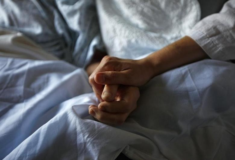 A woman holds the hand of her mother who is dying from cancer during her final hours at a palliative care hospital in Winnipeg July 24, 2010.    REUTERS/Shaun Best