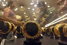 Золотые браслеты в ювелирном магазине в Калькутте. 21 апреля 2015 года. Цены на золото снизились с двухнедельного максимума, так как вернувшиеся на рынок китайские трейдеры продают металлы, чтобы зафиксировать прибыль. REUTERS/Rupak De Chowdhuri