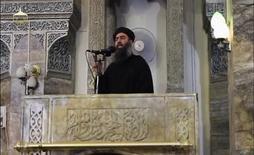 """Мужчина, предположительно Абу Бакр аль-Багдади, выступает с речью в мечети в Мосуле. Восемь высокопоставленных членов """"Исламского государства"""" погибли в результате воздушной атаки во время встречи в городе на западе Ирака, но лидера группы Абу Бакра аль-Багдади, судя по всему, среди них не было, сообщили жители города и источники из больниц. REUTERS/Social Media Website via Reuters TV"""