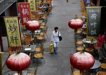 A woman carrying a shopping bag walks underneath lanterns of a restaurant in a shopping district of Beijing, China, September 22, 2015. REUTERS/Kim Kyung-Hoon